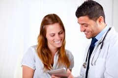 Doctor latino y un paciente que mira para marcar en la tableta la PC Imágenes de archivo libres de regalías