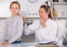 Doctor leading medical appointment the girl with stethoscope Stock Images