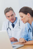 Doctor listening attentively to a colleague Stock Image