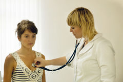 Doctor listening   patient with  stethoscope Stock Photography