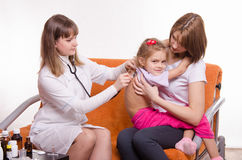 Doctor listening stethoscope back at girl sitting in hands of mother Stock Photography