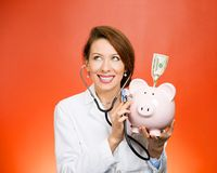 Doctor listening with stethoscope to piggy bank. Portrait happy health care professional, doctor, nurse listening with stethoscope to piggy bank, dollar bill royalty free stock photos