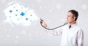 Doctor listening to abstract cloud with medical signs. Proffesional doctor listening to abstract cloud with medical signs Stock Images