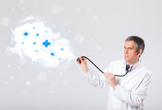 Doctor listening to abstract cloud with medical signs Royalty Free Stock Photos