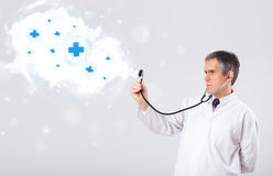 Doctor listening to abstract cloud with medical signs Royalty Free Stock Photography