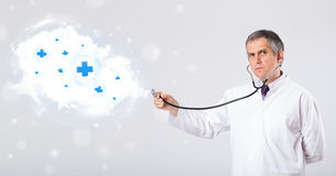 Doctor listening to abstract cloud with medical signs Stock Image