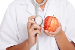 Doctor listening to an apple with a stethoscope Royalty Free Stock Photography