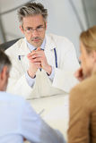 Doctor listening to couple in hospital office Stock Photos