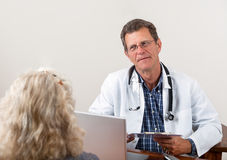 Doctor Listening to Female Patient in Office Royalty Free Stock Images