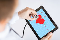 Doctor listening to heart beat Stock Photo