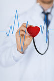 Doctor listening to heart beat stock images