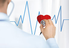 Doctor listening to heart beat Stock Photography