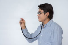 Doctor listening to a heartbeat with a stethoscope over white background. Doctor with a stethoscope holding the disk towards the camera in a medical concept with Royalty Free Stock Photos