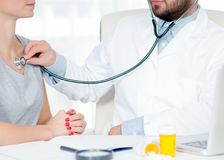 Doctor listening to patient chest with stethoscope. Checking heart beat of patient royalty free stock image