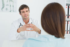 Doctor listening to patient with concentration in medical office Royalty Free Stock Images