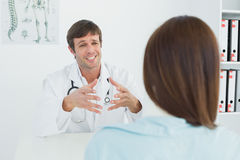 Doctor listening to patient with concentration in medical office Stock Photos