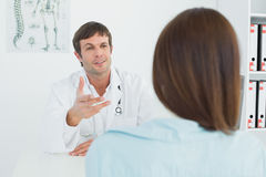 Doctor listening to patient with concentration at medical office Royalty Free Stock Photo
