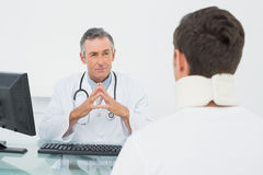 Doctor listening to patient with concentration in office Stock Photography