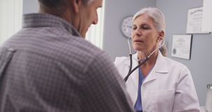 Doctor listening to patient's heart rate with stethoscope.  Stock Photography