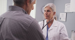 Doctor listening to patient's heart rate with stethoscope Royalty Free Stock Photos