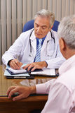 Doctor listening to patient and taking notes Royalty Free Stock Photo