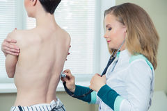 Doctor listening to patients chest with stethoscope in his office at the hospital Stock Image