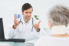 Doctor listening to senior patient at medical office Royalty Free Stock Images