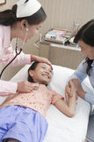 Doctor a Listens al latido del corazón de la niña, muchacha está sonriendo Fotos de archivo