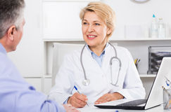 Doctor listens to mature patient. And fills polling form stock photography
