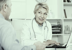 Doctor listens to mature patient. Doctor interviews mature patient and fills data in computer database royalty free stock photo