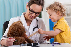 Doctor and little boy examining a teddy bear Royalty Free Stock Photo