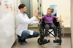 Doctor and little child in wheelchair. At hospital stock photos