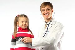The doctor and the little girl. The doctor in a white dressing gown and the little girl at it on reception Stock Photos