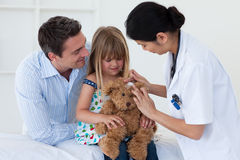Doctor and little girl examing a teddy bear Royalty Free Stock Photography