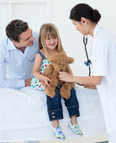 Doctor and little girl examining a teddy bear Stock Images