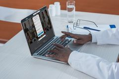 Doctor with loaded LinkedIn website. Cropped image of african american doctor with loaded LinkedIn website Royalty Free Stock Photography