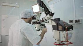 Doctor  loking at monitor at big microscope system stock footage