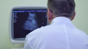Doctor look at screen of ultrasound equipment. The doctor checking the abdomen of patient stock video footage