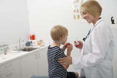 Doctor Looking At Boy Taking Medicine. Boy taking medicine while female doctor looking at him in the clinic stock photo
