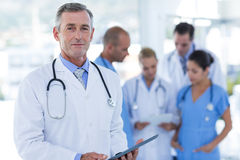 Doctor looking at camera while his colleague discussing Stock Photos