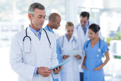 Doctor looking at clipboard while his colleague discussing Stock Photos