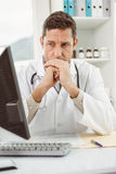 Doctor looking at computer in medical office Royalty Free Stock Photography