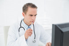 Doctor looking at computer at medical office Royalty Free Stock Photo