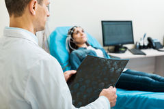 Doctor looking through CT results while conducting electroencephalography. Considering all details. Pleasant middle-aged men examining the results of computer Stock Photo
