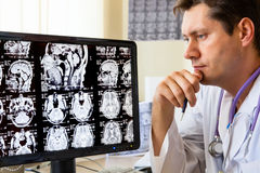 Doctor looking at ct scan. Doctor in hospital looking at ct scan Royalty Free Stock Image