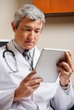 Doctor Looking At Digital Tablet Royalty Free Stock Image