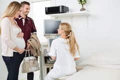 Doctor Looking At Expectant Couple In Clinic Royalty Free Stock Photos