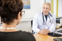 Doctor Looking At Female Patient At Desk. Confident mature doctor looking at female patient at desk in clinic stock photo