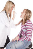 Doctor looking into females mouth royalty free stock image