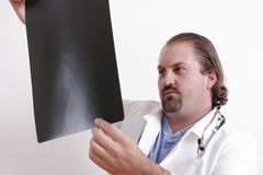 Doctor looking at a film. Doctor in a white coat holds up an x-ray Stock Photos